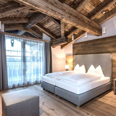 Doublebed with wooden back wall and seat in the PURADIES Hotel & Chalet in Leogang