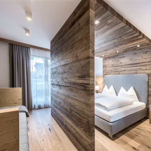 Doublebed with wooden frame and wooden wall in the Delux Suite at Hotel Puradies
