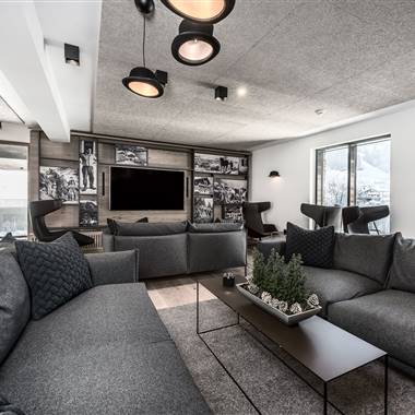 2 large, gray couches in the cigar lounge with flat screen TV
